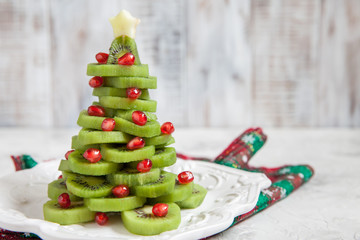 Healthy dessert idea for kids party - funny edible kiwi pomegranate Christmas tree
