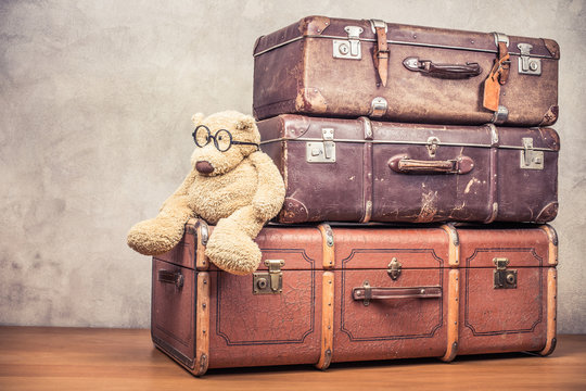 Teddy Bear toy with round specs sitting on vintage old classic big travel leather suitcases on wooden floor. Travel luggage concept. Retro style filtered photo