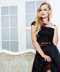 stylish elegant blonde woman in beauty rich interior, wearing black dress smiling, lifestyle people concept