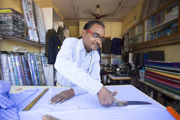Tailor cutting fabric in his shop. India