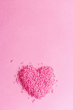 Sprinkles in a heart shape against a pink background