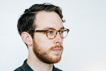 Portrait of young man in apartment wearing glasses