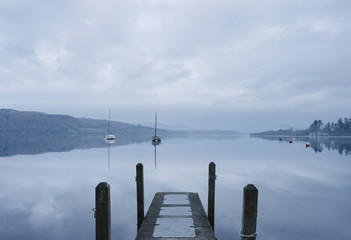Early morning calm reflections with on Lake Windermere. Cumbria, UK.