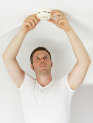 Male technician installing smoke detector at home.