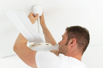 Male technician installing ceiling fan.