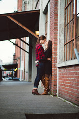 Lesbian couple embrace against brick wall during a date downtown