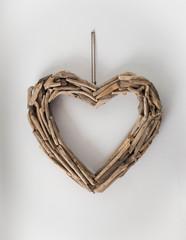 Heart shaped driftwood hanging on a white wall