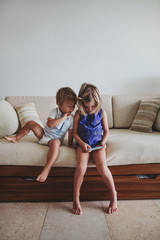 Cute young girl playing with mobile phone with little brother watching