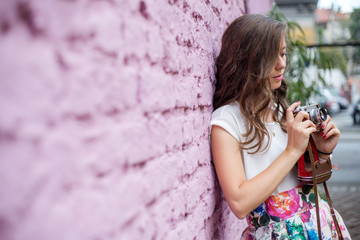 Cute brunette standing next to a pink wall and holding retro camera