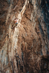 Fit rock climber climbing an extreme cliff face in a mountain