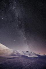 Illuminated ski slopes with night sky