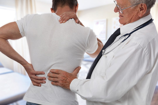 Male Doctor and patient suffering from back pain during medical exam.
