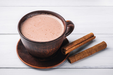 Hot cocoa with milk in brown clay cup and cinnamon sticks on table of white wooden planks