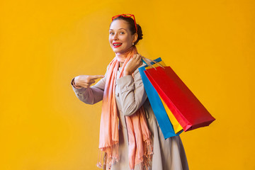 Young adult woman pointing finger on bags and looking at camera and toothy smile. On yellow background.