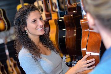 Spoed Foto op Canvas Muziekwinkel Woman in guitar shop