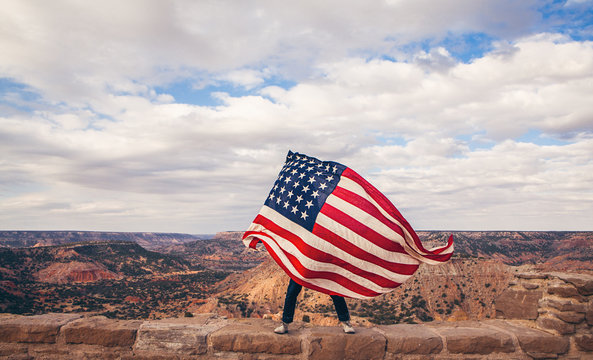 Man waving American flag while standing on canyon