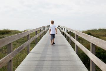 boy walking on a boardwalk toward the beach