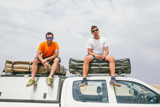 Two young men wearing sunglasses on top of a car on adventure travel