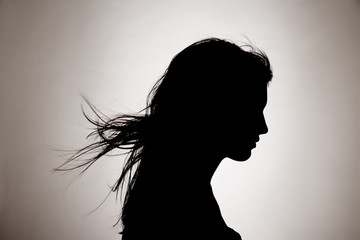 Silhouette of woman with hair blowing in the studio.