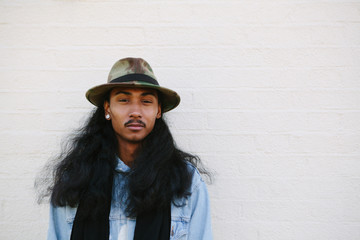 Stylish man with long hair wearing a hat