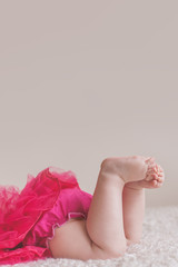 Adorable chubby baby feet and toes with large copy space above. Baby wearing a pink tutu.