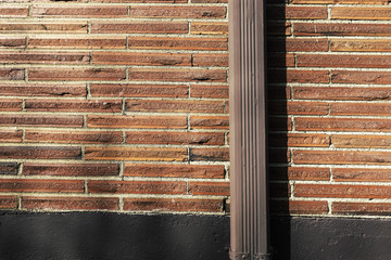 Brick wall and painted brown gutter pipe