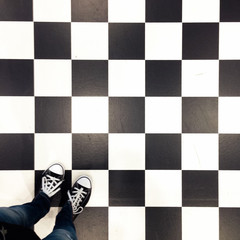 Woman's feet on a black and white checkerboard tiled floor