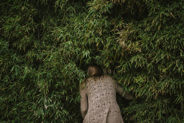 Girl Crouching Into Dense Trees