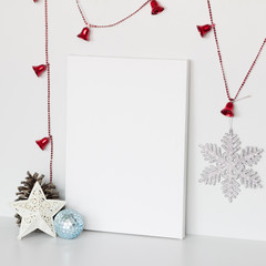 Mock up poster in interior. Blank canvas lean at white wall. Christmas and New Year decoration.