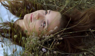 Girl is laying in the grass and flowers on the spring meadow