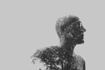 Double exposure of older man and trees in black and white
