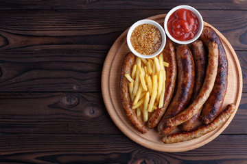 Appetizing beer snacks set. Grilled sausages and french fries served with spicy tomato sauce and mustard on the board, flat lay, free space. Oktoberfest food, pub concept