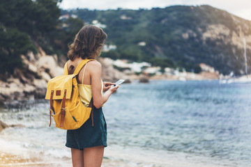 Hipster girl with backpack hold on smart phone gadget in sand coastline. Traveler using in female hand mobile on background beach seascape horizon. Tourist look on blue sun ocean, summer lifestyle