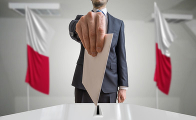 Election or referendum in Poland. Voter holds envelope in hand above ballot. Polish flags in background.