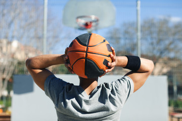 Back view of a male basketball player holding a ball in an urban court.