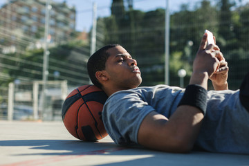 Male basketball player using his smartphone resting after training session.