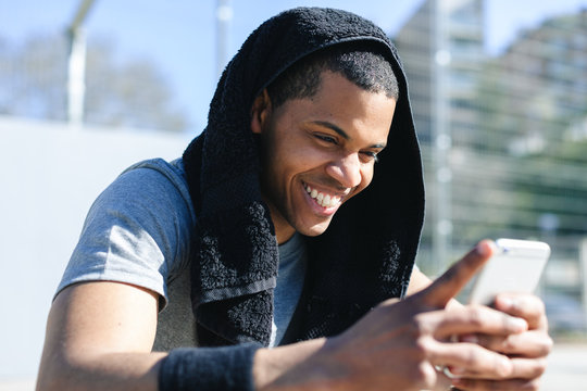 Male basketball player using his smartphone after training session.