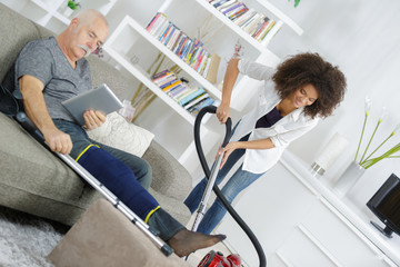 senior man relaxing while young woman is cleaning the house