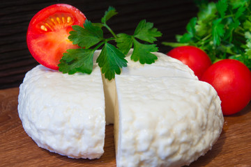 Young oak cheese cutting Board with tomatoes and parsley. Mozarella for pizzas and salads. Wall mural