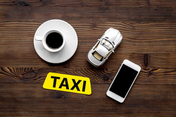 call a taxi with mobile app and cup of coffee wooden table background top view copyspace