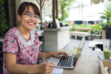 Cute student using laptop and smiling