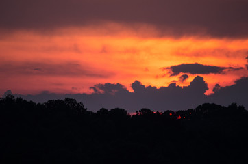 A summer sunset behind layers of clouds near Coldwater, Alabama, USA