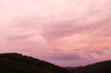 Pre-sunrise clouds take on unusual colors as the sun nears the horizon in the hills near Anniston, Alabama, USA