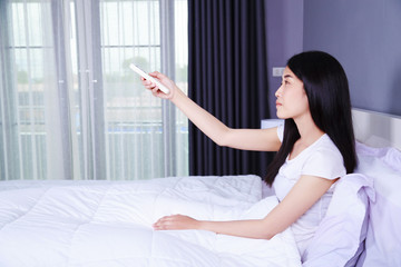 woman hand hold remote air conditioner on bed in bedroom