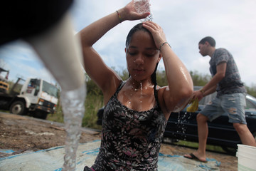 Madelyn Matos washes her hair with mountain spring water, after Hurricane Maria hit the island, in Corozal