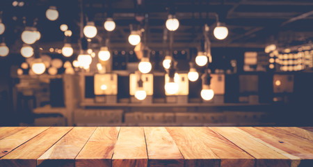 Wood table top on blurred of counter cafe shop with light bulb background.For montage product display or design key visual