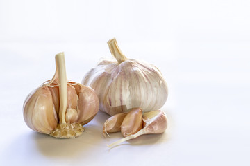 Garlic bulbs and cloves closeup on white background