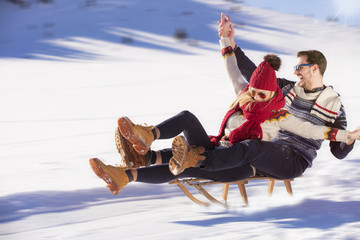 Young Couple Sledding And Enjoying On Sunny Winter Day