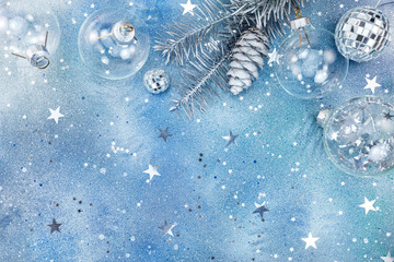 silver christmas decorations on glittering background with star confetti
