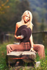 Sexy naked country girl covering her breast with a cowboy hat and sitting on a wooden bench  - portrait outdoor with a fence on the background